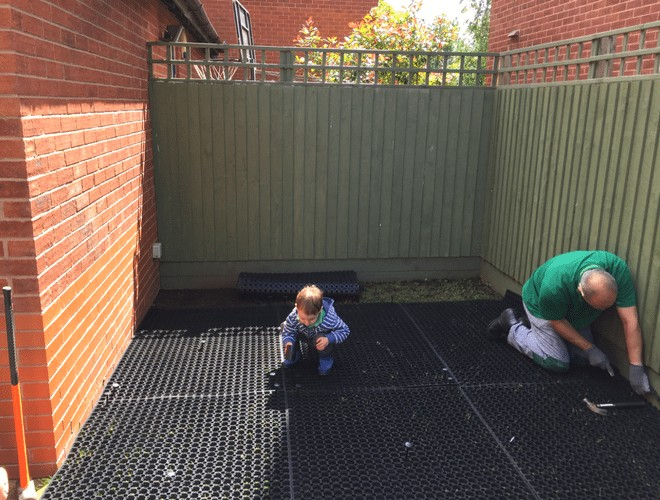 Rubber Grass Mats Being Installed Under Playhouse